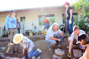 Co-op workshop attendees create passive and active rainwater harvesting systems at a home in the Palo Verde neighborhood on Aug 5, 2017. Here, they are working on digging basins that will passively capture rainwater, and will line the basins with rocks so the basins do not erode during a heavy rain. Photo: Jamie Manser/Watershed Management Group