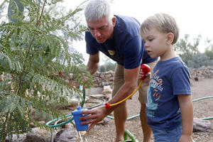 Tucsonan Scott Mencke, and his 3-year-old son, Reef, use water from their water harvesting cistern to water their garden