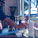 Jaime serves up hot espresso drinks from Peddler on the Path Mobile Cafe.