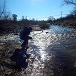 Student walking through a flowing Tucson River