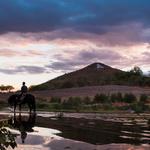 A rider and his horse enjoy the Santa Cruz River at dusk. Photo by Julius Schlosburg