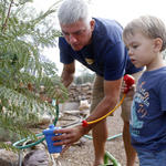Tucsonan Scott Mencke, and his 3-year-old son, Reef, use water from their water havesting cistern to water their garden at home.