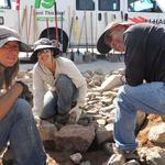 Volunteers place rocks to stabilize basins